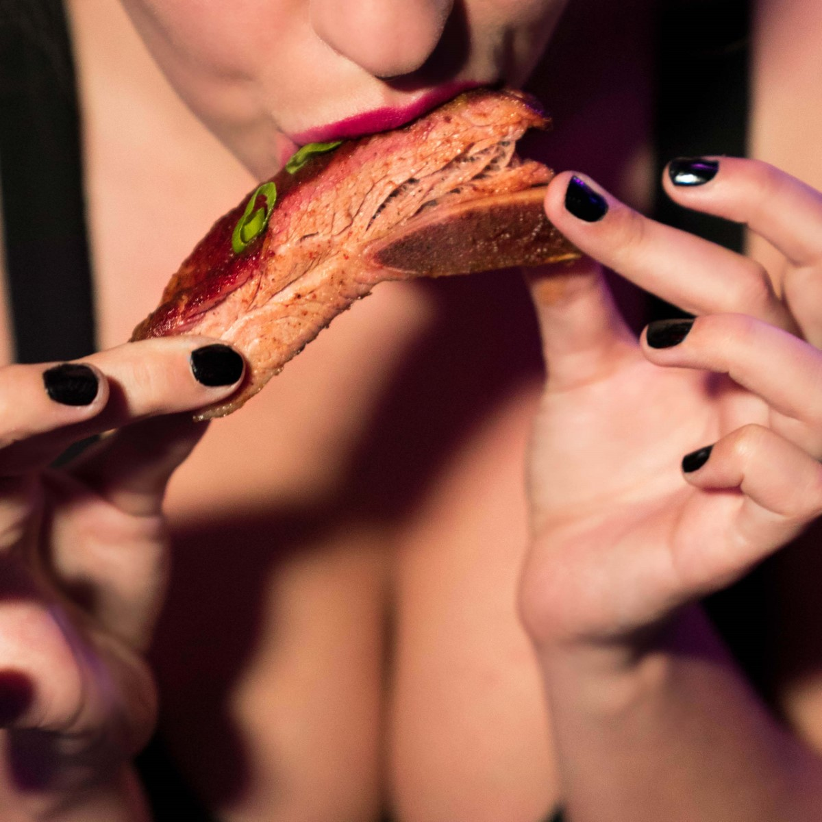 Sexy woman biting into a tbone steak at Primal Cut Steakhouse