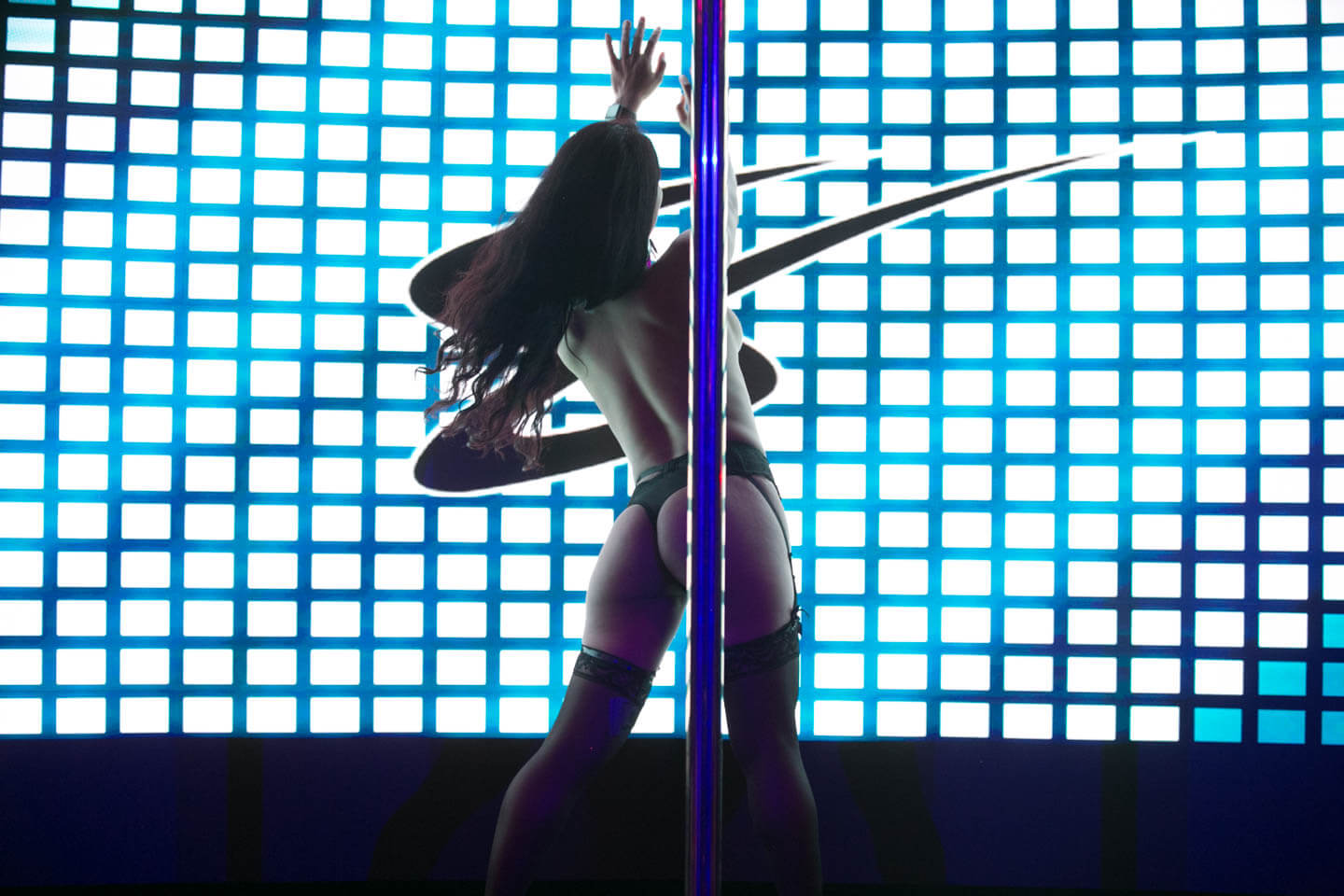 photo of an exotic entertainer on stage grabbing the pole